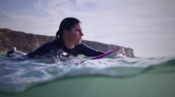 Joana Andrade paddling on a surfboard