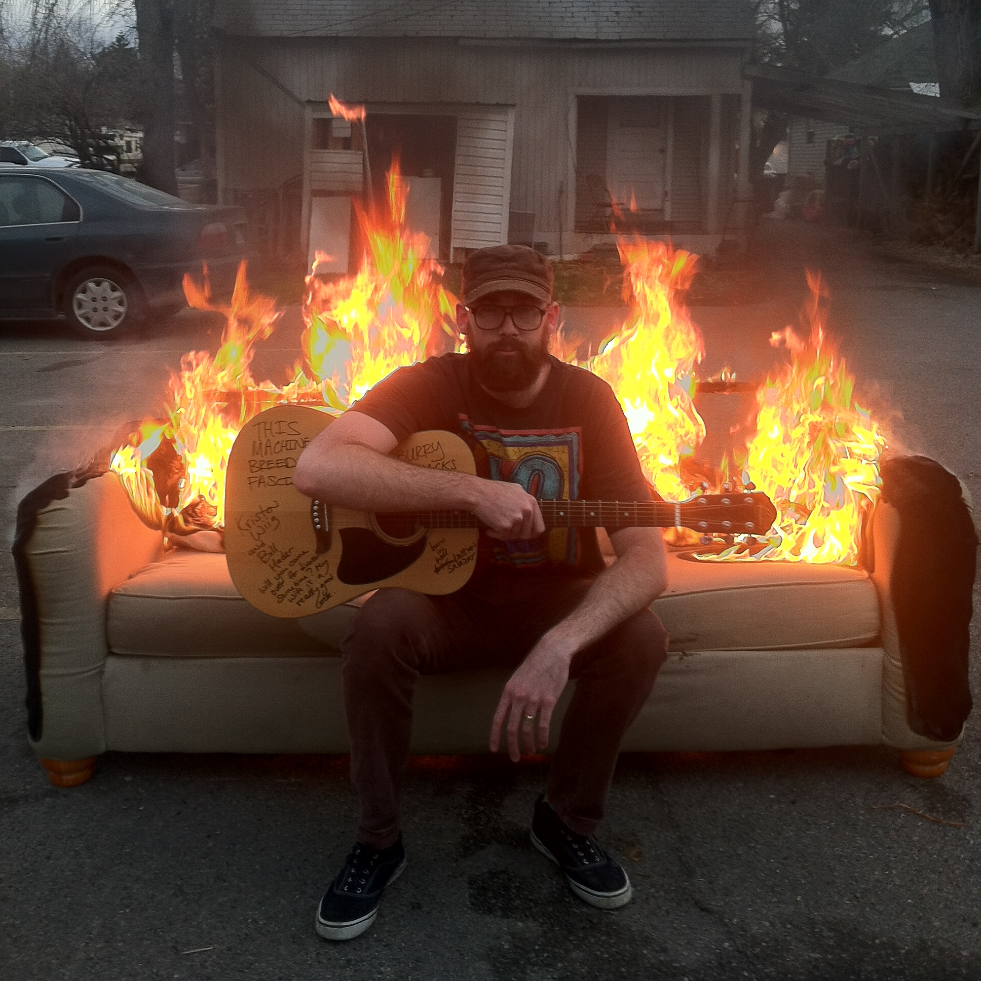 Dre Danburry sat on a sofa with fire behind him.