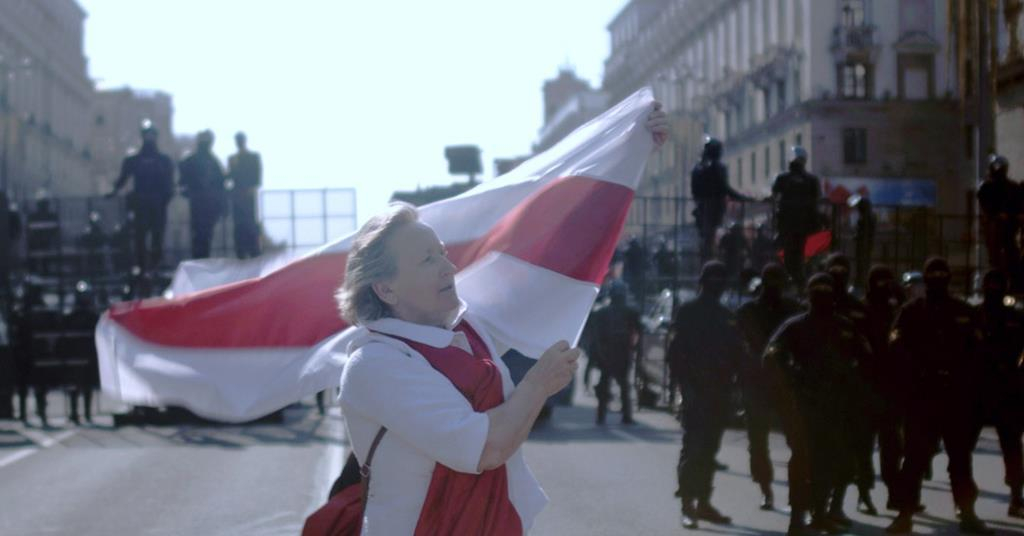 Protester carrying a Belarus flag in-front of the police